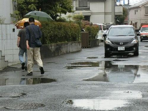 少しの雨でも道の両側が水浸しで歩けない=池田5丁目の私道